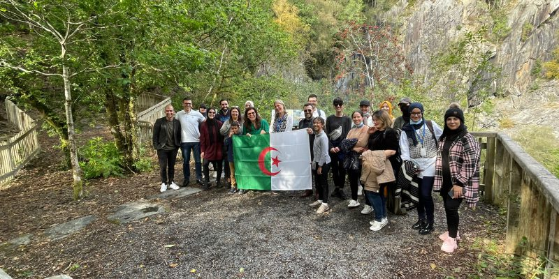 Group holding Algerian flag outside in nature