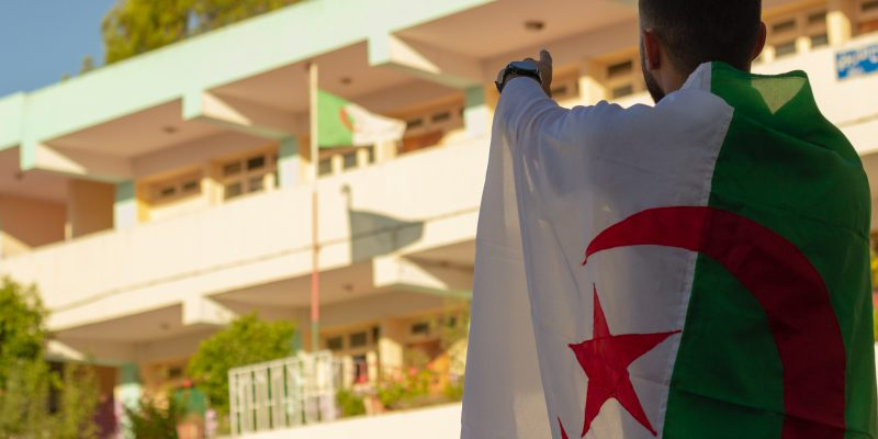 Man in Algerian flag points to sky